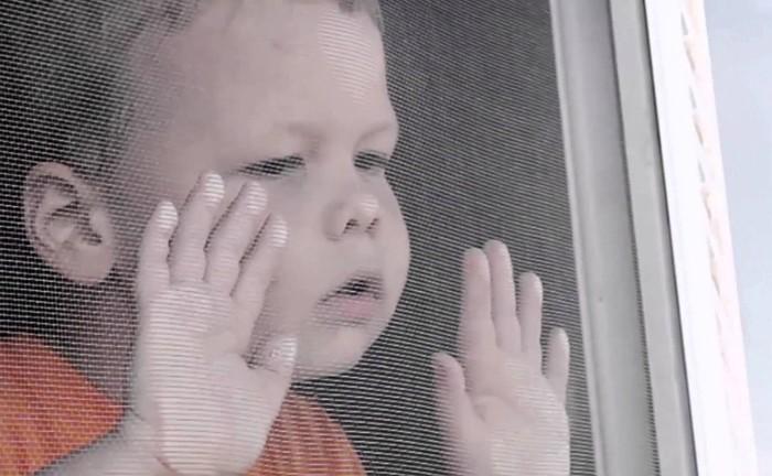 Ребенок опирается на москитную сетку